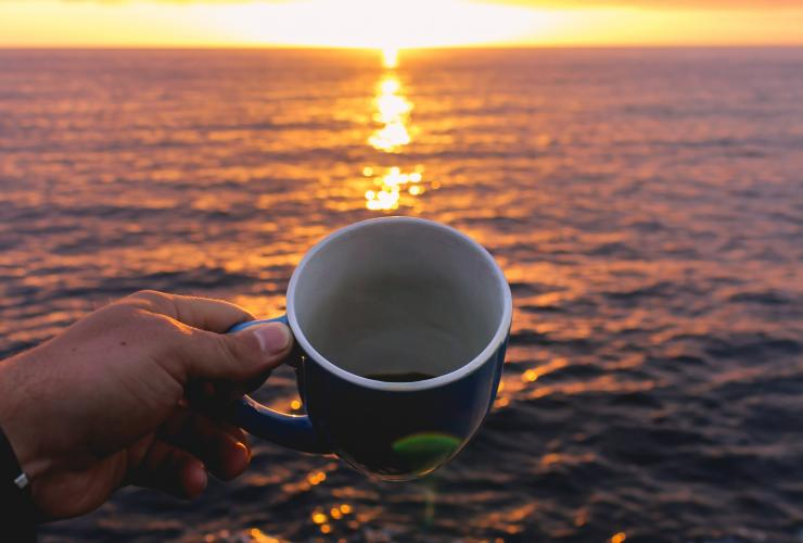 A person holding a blue coffee cup while looking at the sunrise over the sea.
