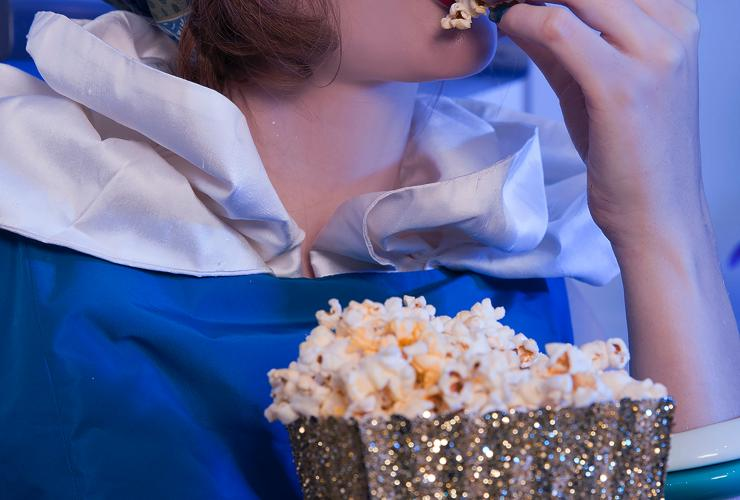 A woman with red lipstick puts popcorn in her mouth
