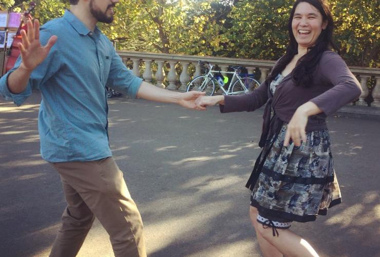A man and a woman happily swing dance in the park.