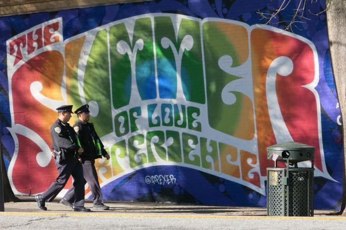 """Picture of the text """"Summer of Love"""" in rainbow letters with two police officers walking by on the sidewalk."""