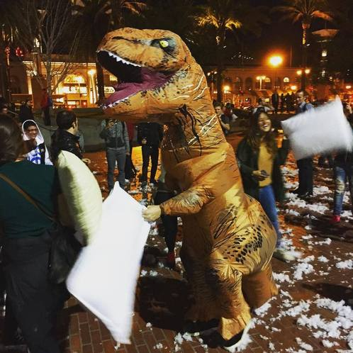 A person in a large T Rex costume participates in the Valentine's Day Pillow Fight in San Francisco.